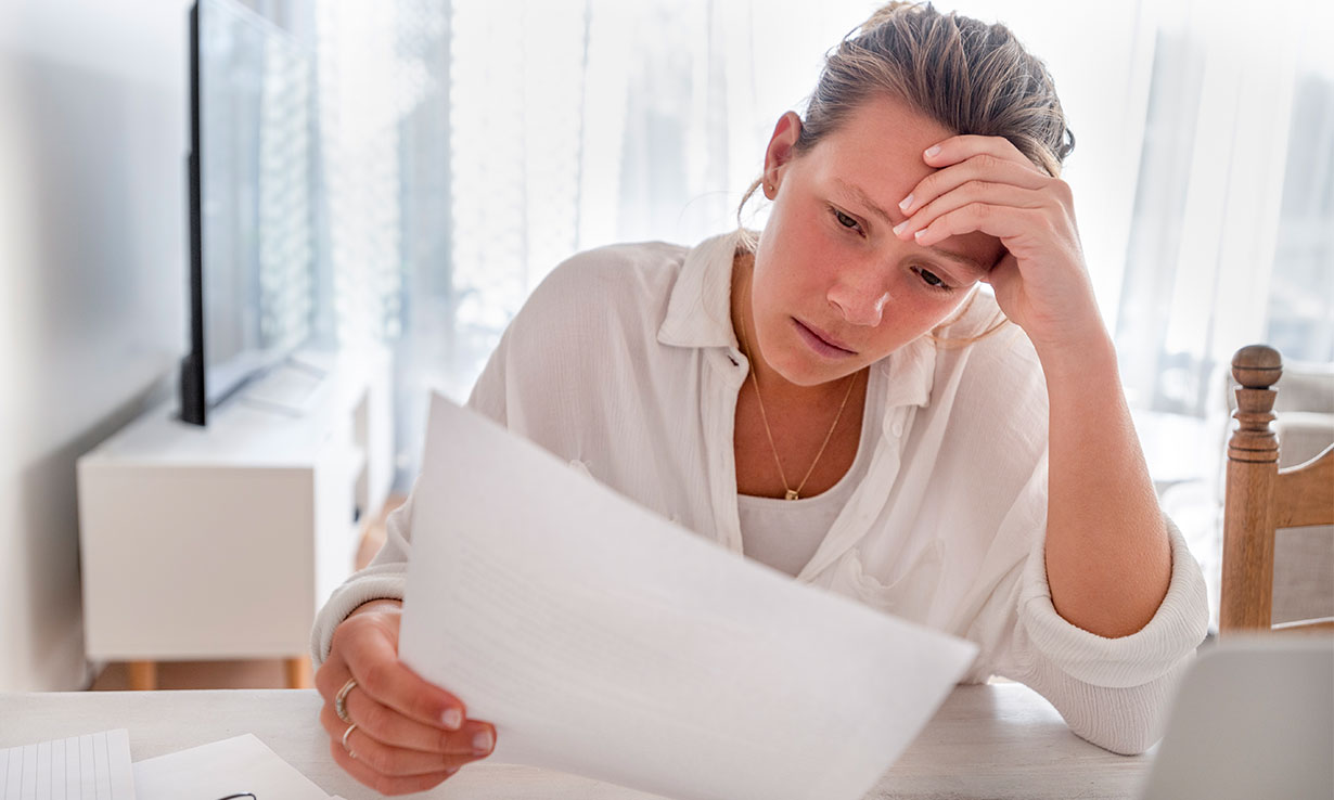 Woman reading her energy bill and looking worried