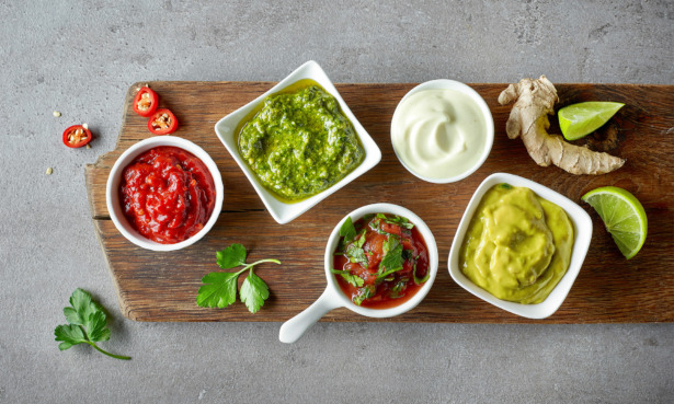 Board of dips including salsa, guacamole and mayo
