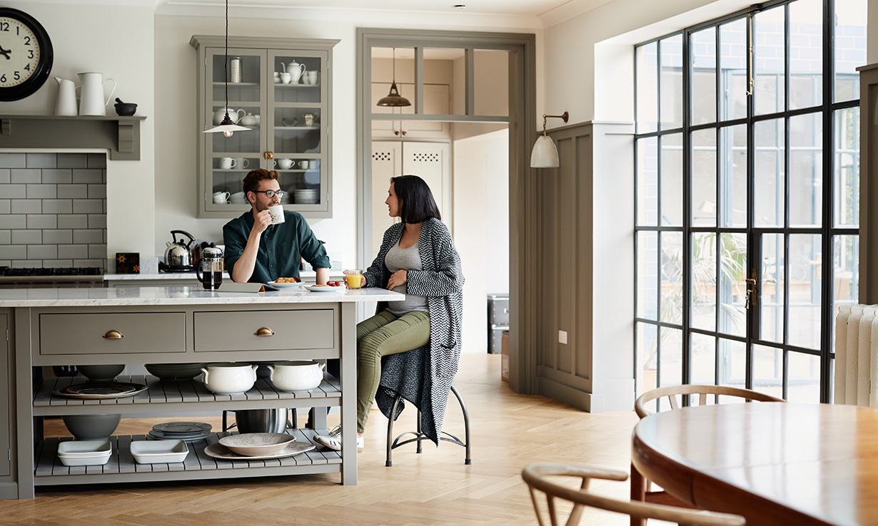 Man and woman eating breakfast at a kitchen island