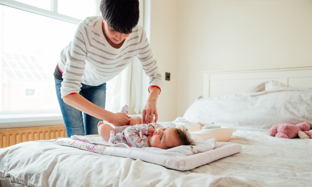 mum changing baby's nappy on a changing mat
