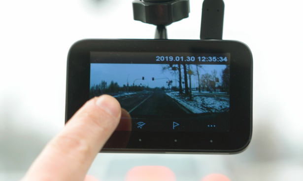 Someone reviewing footage on a dash cam screen