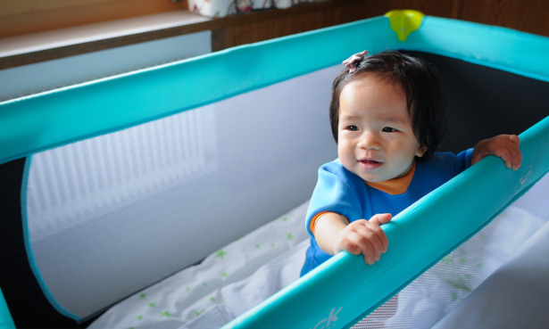 baby in travel cot with mesh sides