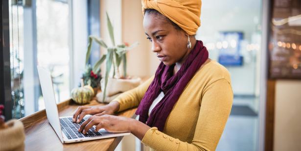 Woman using laptop to research bike insurance