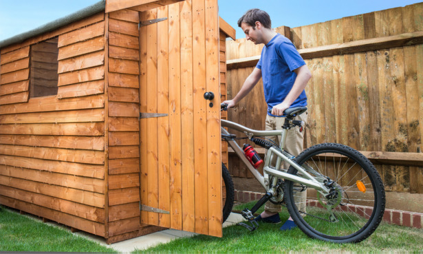 Man putting bike away in the shed