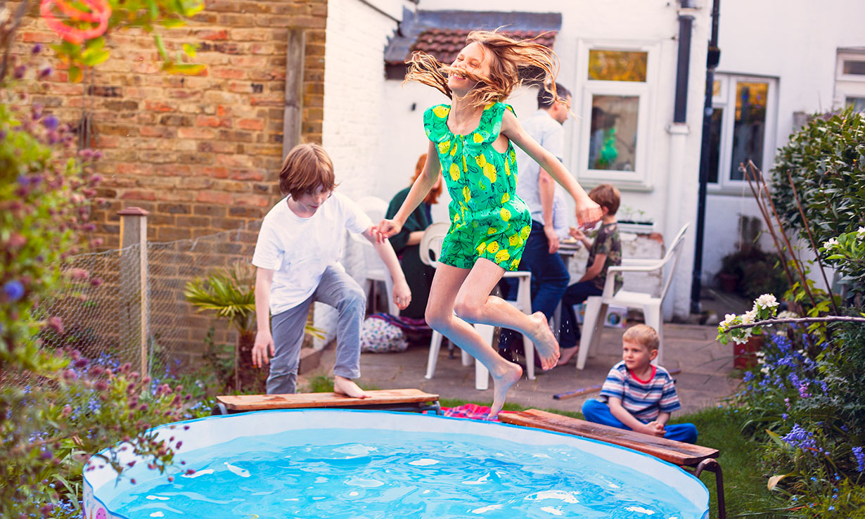 Children jumping into a paddling pool in the sunshine