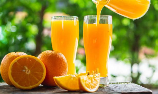 Oranges next to glasses of orange juice