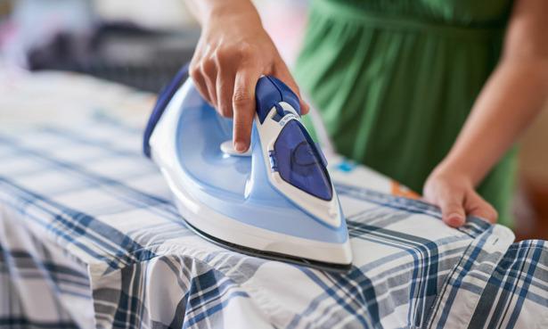 Woman ironing chequered shirt
