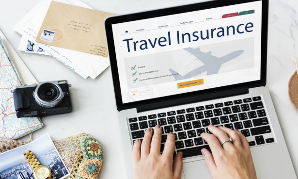 someone booking travel insurance on a laptop