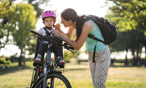 Baby wearing helmet on bicycle