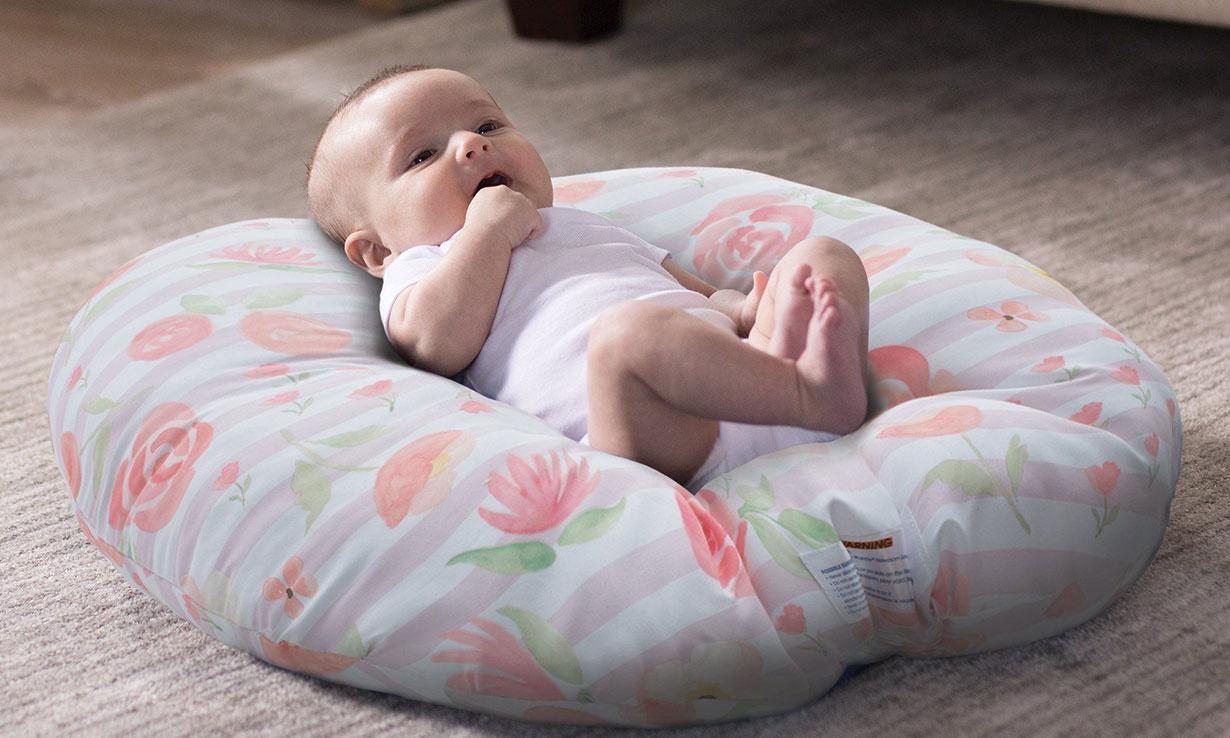 A baby on a newborn lounger pillow