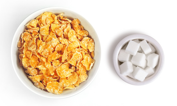 Bowl of cornflakes next to bowl of sugar cubes