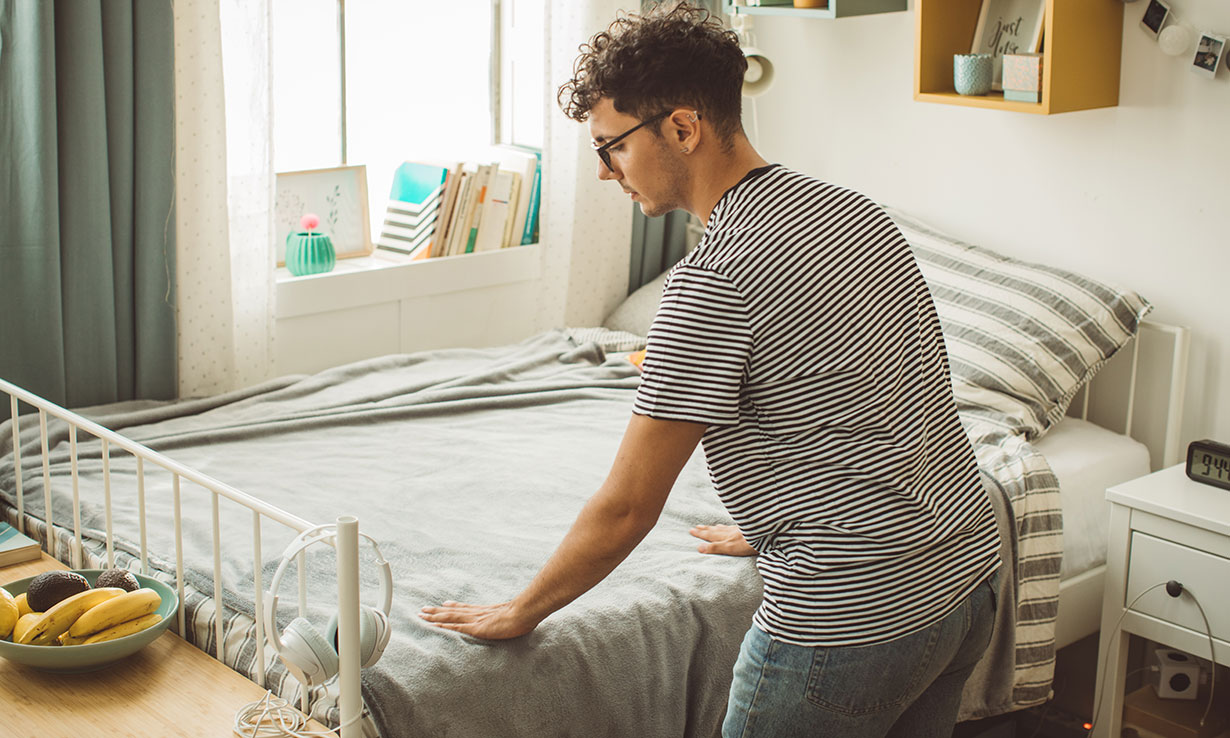 Uni student making bed in halls