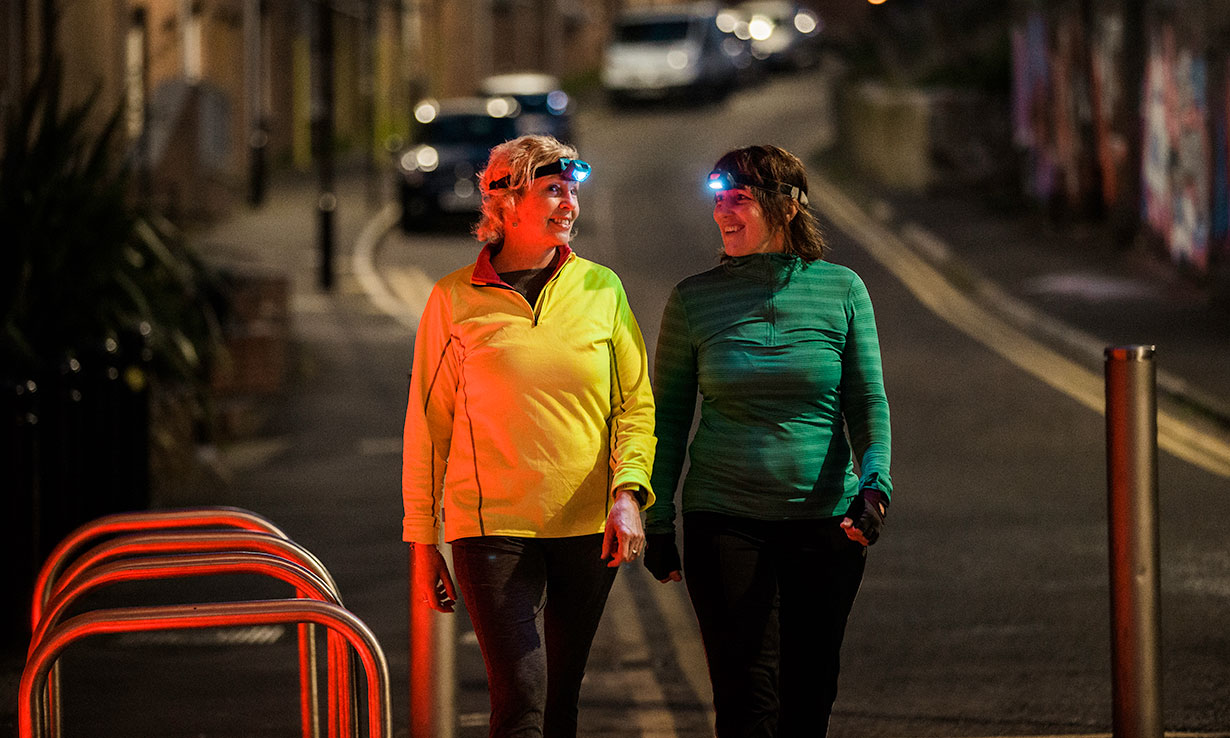 Women wearing head torches at night