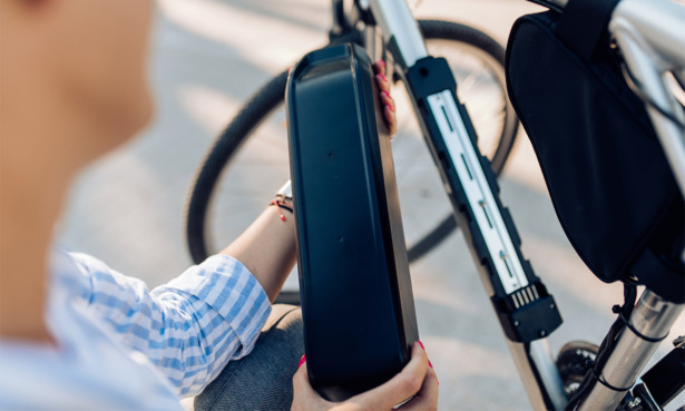 cyclist putting battery into e-bike motor