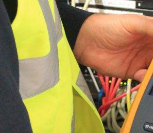 Engineer testing fibre cables in server room, fibre optic courses in essex