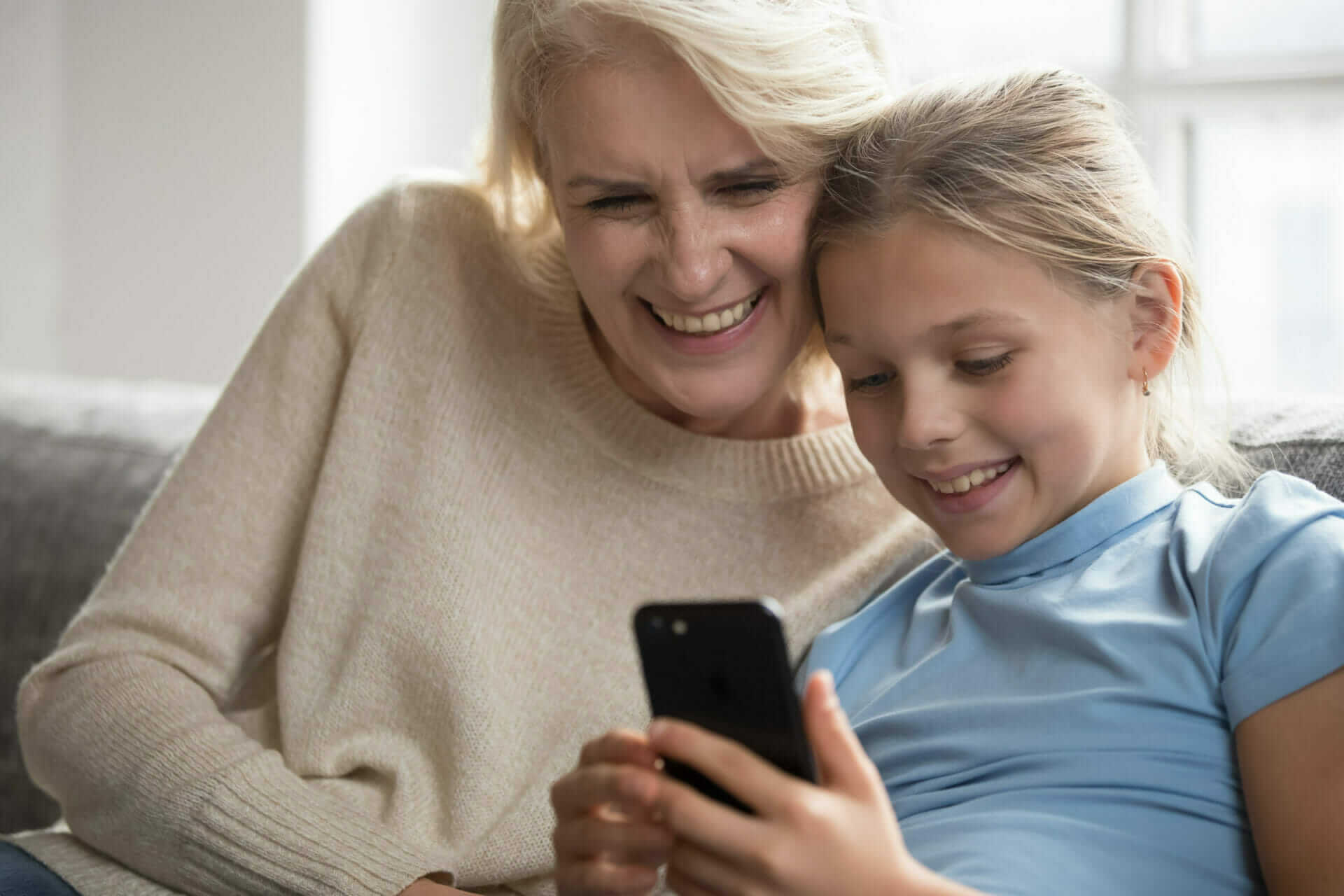 A photo of a woman and child looking at a mobile phone screen
