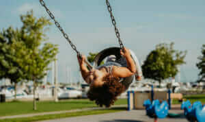 Child playing on a swing in a park. Materials from recycled electricals can be remanufactured into children's playground equipment.