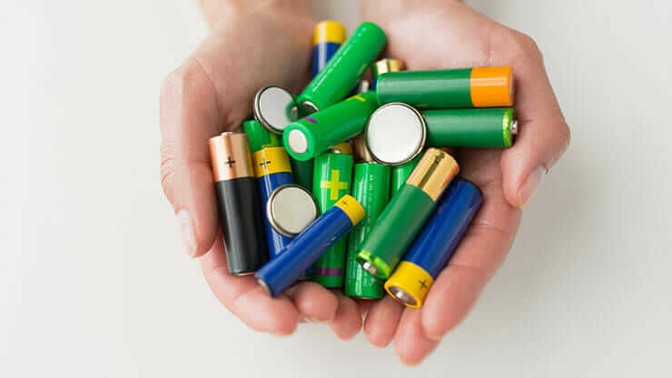 hands holding batteries to be recycled