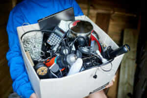 photo of person holding box of old electrical items