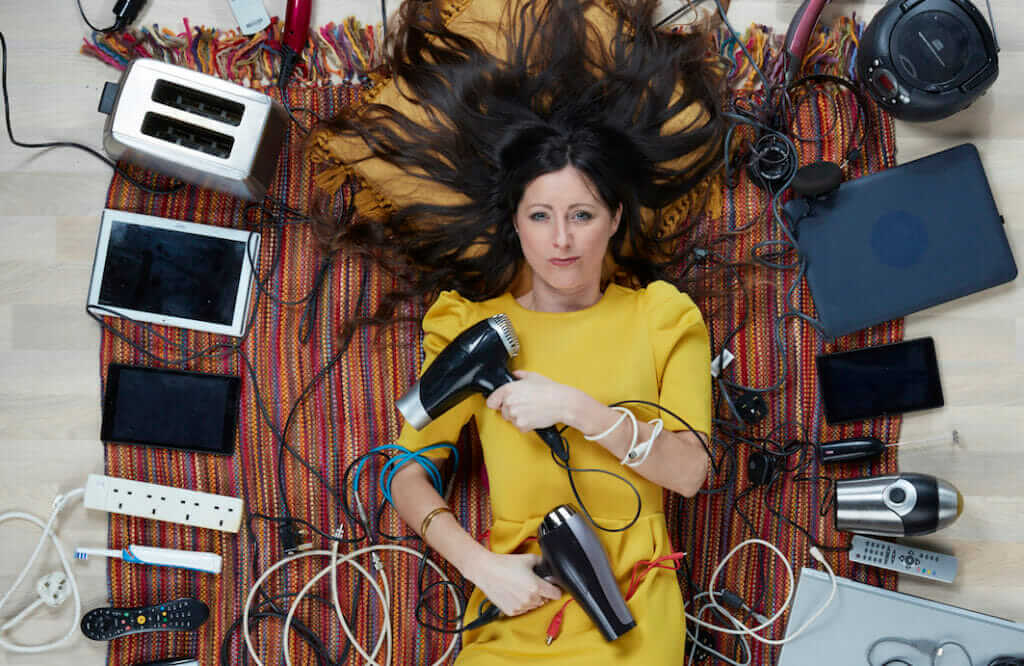 Natalie Fee, lying among electricals, by Gregg Segal