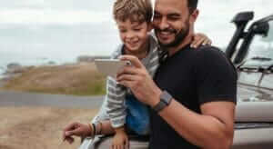 man and boy using electronic devices