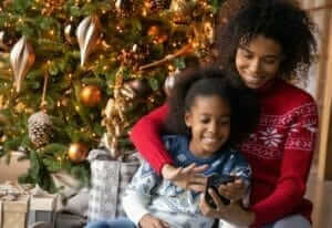 woman and child with mobile phone at christmas