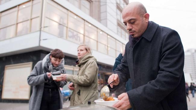 Un réfugié syrien nourrit des SDF allemands