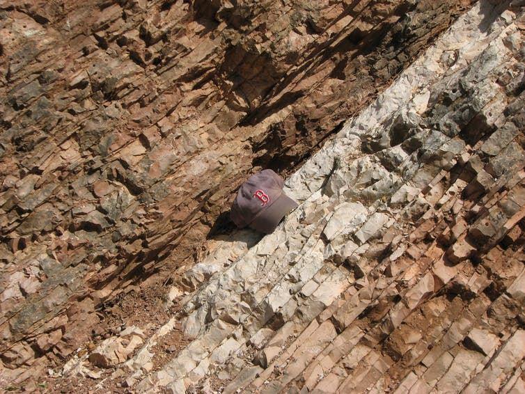 Les roches près de Gubbio, en Italie, changent de couleur et de texture à la ligne indiquant l'événement d'extinction du Crétacé-Paléogène qui a anéanti les dinosaures il y a 66 millions d'années. Une casquette de baseball montre une échelle - Crédit : Robert DeConto et Mark Leckie, UMass Geosciences, CC BY-ND
