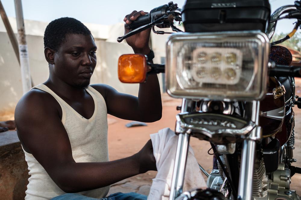 Un pilote de zémidjan (taxi moto) à Lomé nettoie son vélo de façon obsessionnelle - Crédit : Nyani Quarmyne chez Panos pour Mosaic