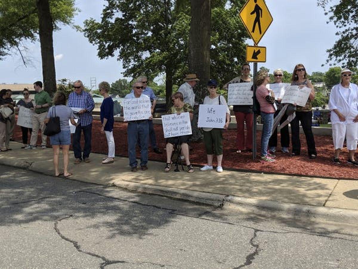 Les gens tiennent des pancartes avec des versets bibliques pour protester contre le dévoilement par le Temple satanique de sa statue de la chèvre ailée Baphomet à Little Rock, Arkansas en août 2018. AP Photo / Hannah Grabenstein