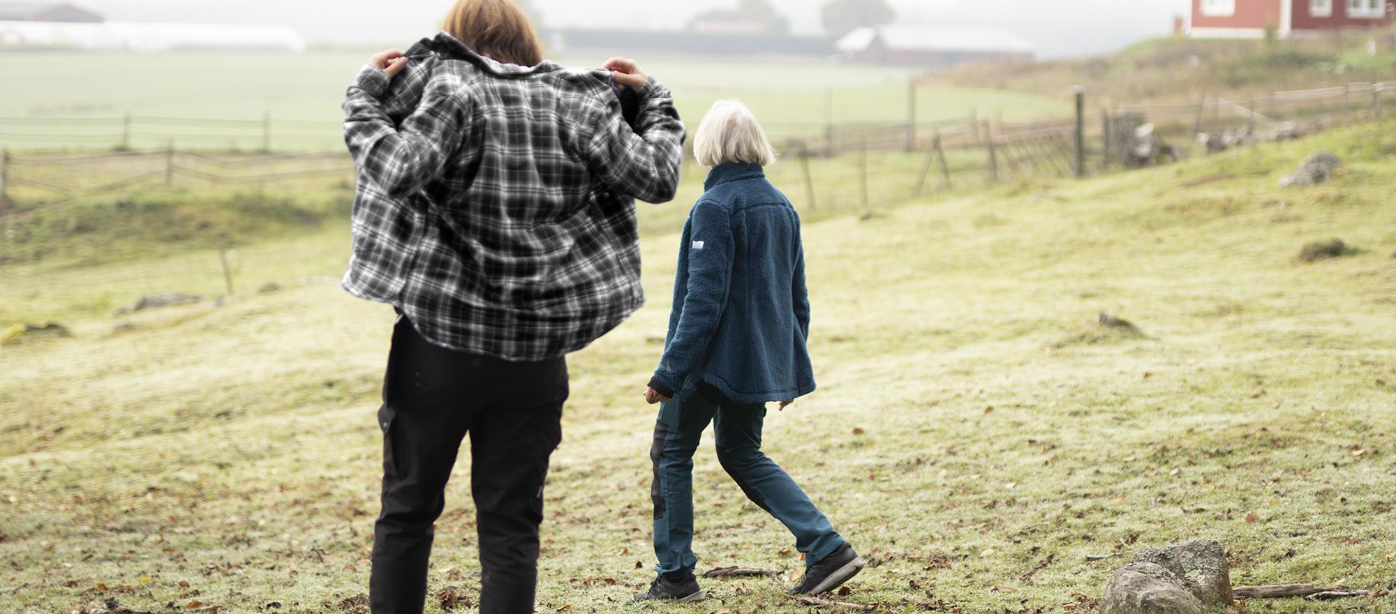 Två kvinnliga bönder går i en hästhage och sätter på sig sin arbetsskjorta