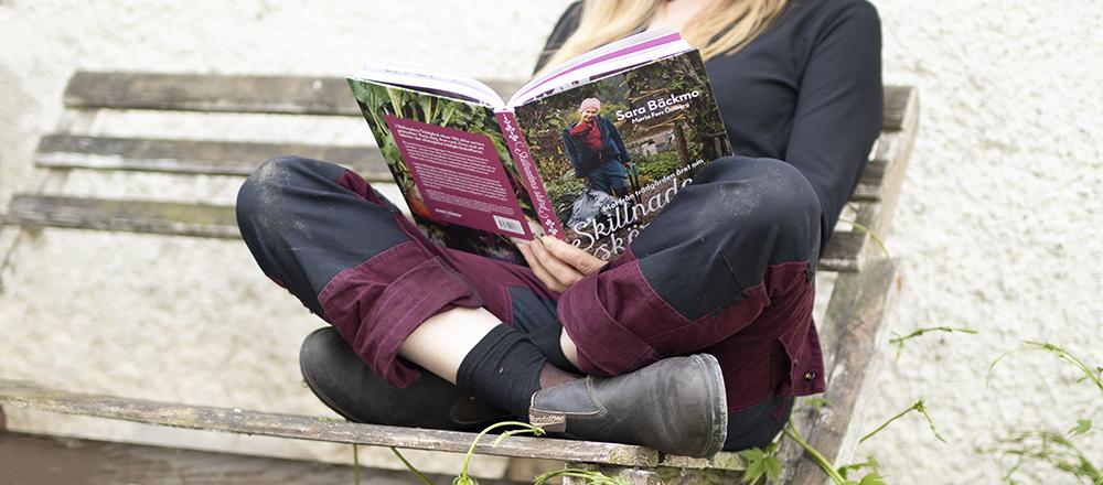 Kvinna sitter i sina vinröda trädgårdsbyxor och läser en bok om odling.