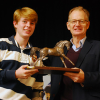 Conor Crozier of Hope in the Valley receives the Cowan Trophy from Phillip Mumford