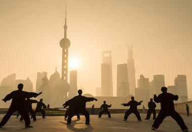 A group practices tai chi in front of Shanghai's skyline