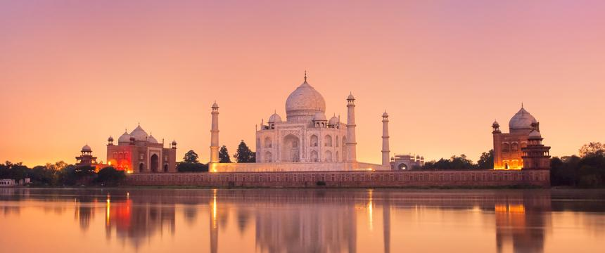 A view over the water to the Taj Mahal in Agra at sunset