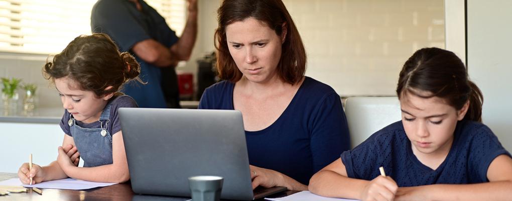 Mutter sitzt mit ihren beiden lernenden Kindern am Tisch und schaut auf den Laptop