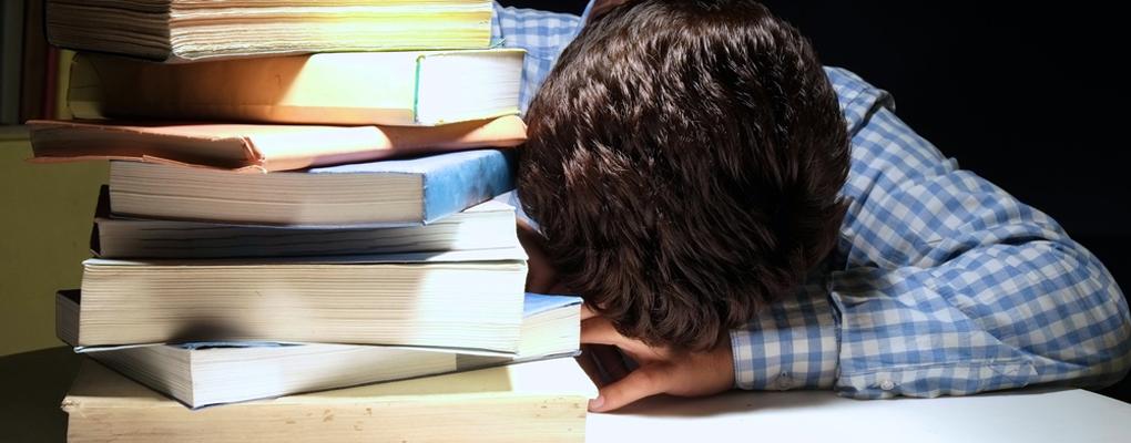 Ein Junge legt seinen Kopf auf einen Tisch voller Bücher