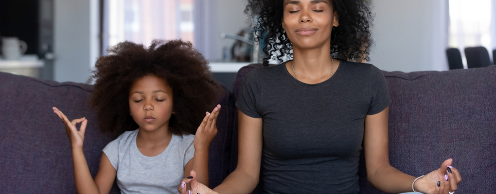 Eine Mutter und ihre Tochter sitzen in einer Yoga-Pose auf einer Couch
