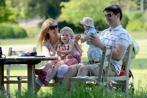 A family relaxing at West Dean Gardens