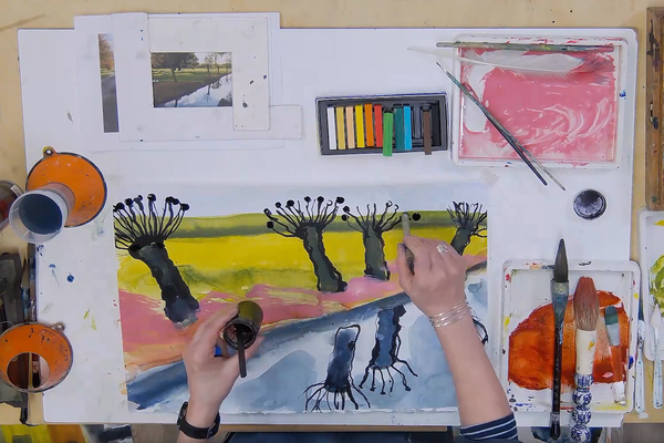 A birds eye view of Melanie's desk with her painting and materials on