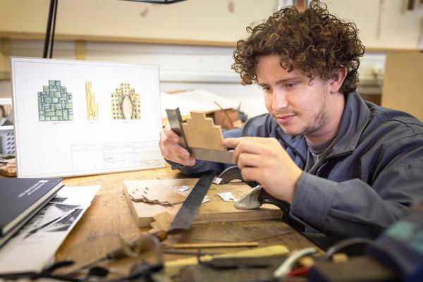 Finn Banwell at his workbench in the metals workshop, with his design in the background. Image credit: Chris Ison